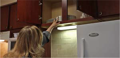 Madonna reaches a high kitchen cabinet
