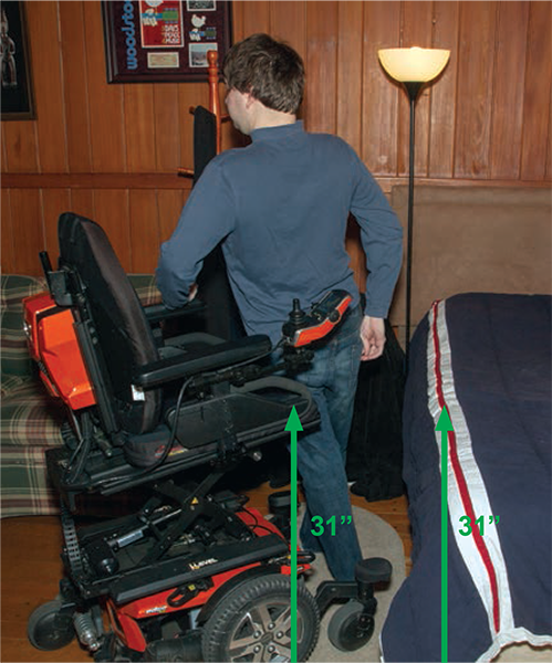 Josh does a stand-pivot transfer independently while holding on to the armrests of the chair.